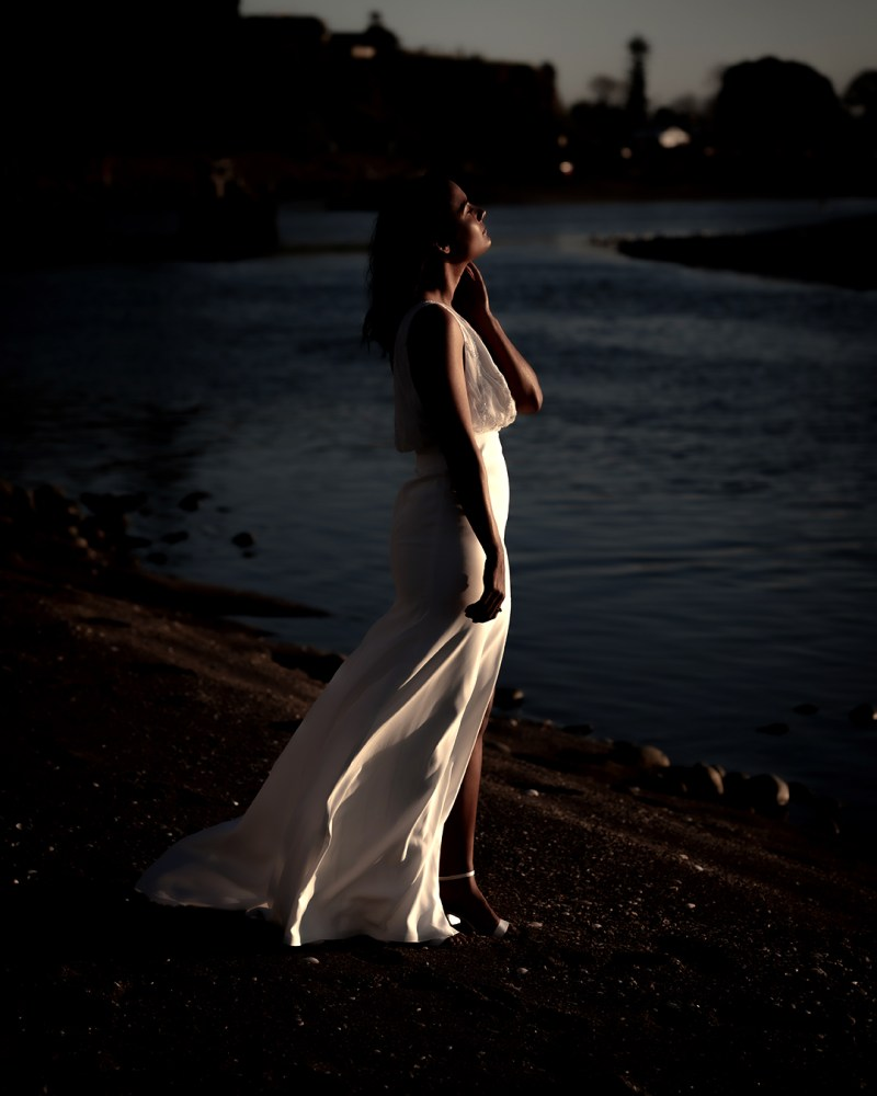 A woman stands in the sun whilst wearing a White Silk Bridal dress
