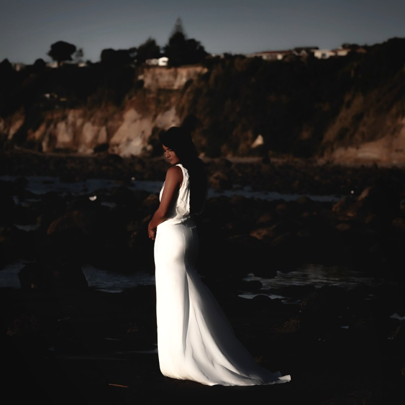 A woman wears a bridal gown whilst standing on a beach in the Bay of Plenty