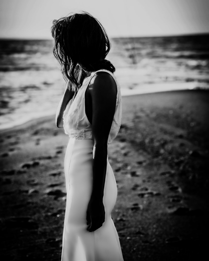 A woman stands on a beach whilst wearing a bridal gown