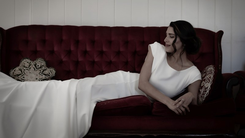 A woman in a white wedding dress lies on a red sofa in a Tauranga music venue
