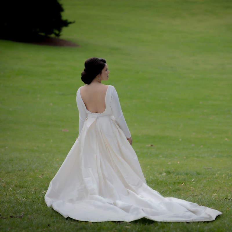 A woman in a bridal gown stands on the grass at an Auckland park