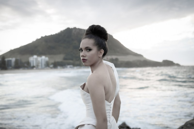 A woman stands by the sea whilst wearing a White Silk Bridal wedding dress