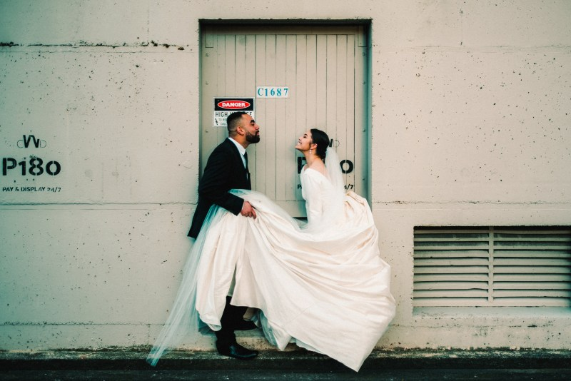 A woman in a white bridal gown blows a kiss at her husband