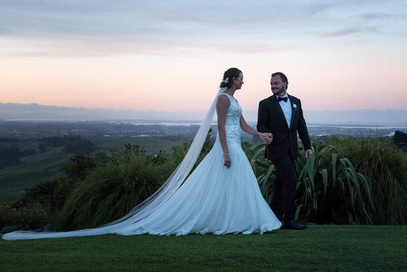 A groom leads his bride, wearing a white wedding dress, across grass after their wedding