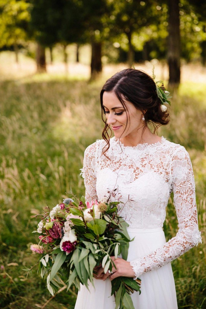 A bride in a white wedding dress stands in a field holding a bunch of flowers looking very happy
