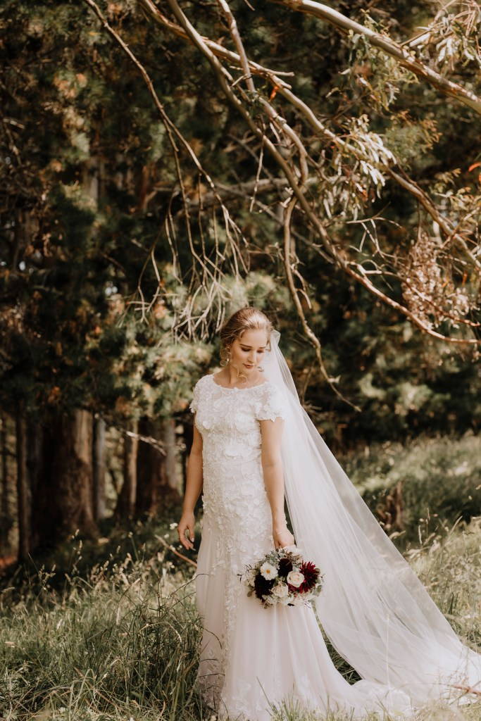 A bride in a white wedding dress stands in a forest