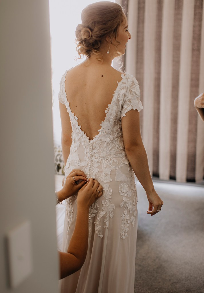 The back of a bridal gown is fastened as the bride stands still