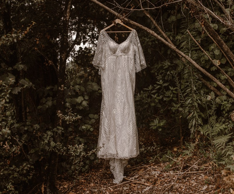 A white bridal gown hangs from a tree branch waiting to be worn