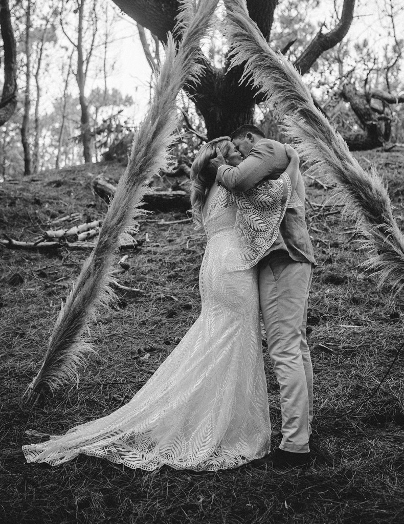 A couple newly married kiss in a clearing in a forest