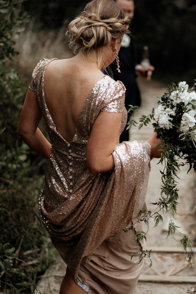A woman holding flowers and wearing a sparkly bridal gown walks down steps