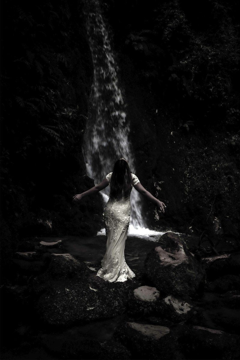 a woman in a bridal gown stands in front of a waterfall