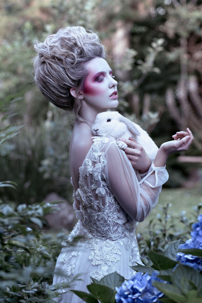 A woman in a white wedding dress holds a rabbit