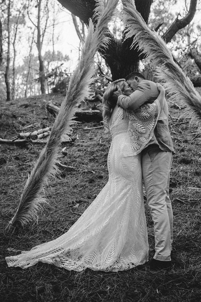 A bride and groom kiss in a wooded area