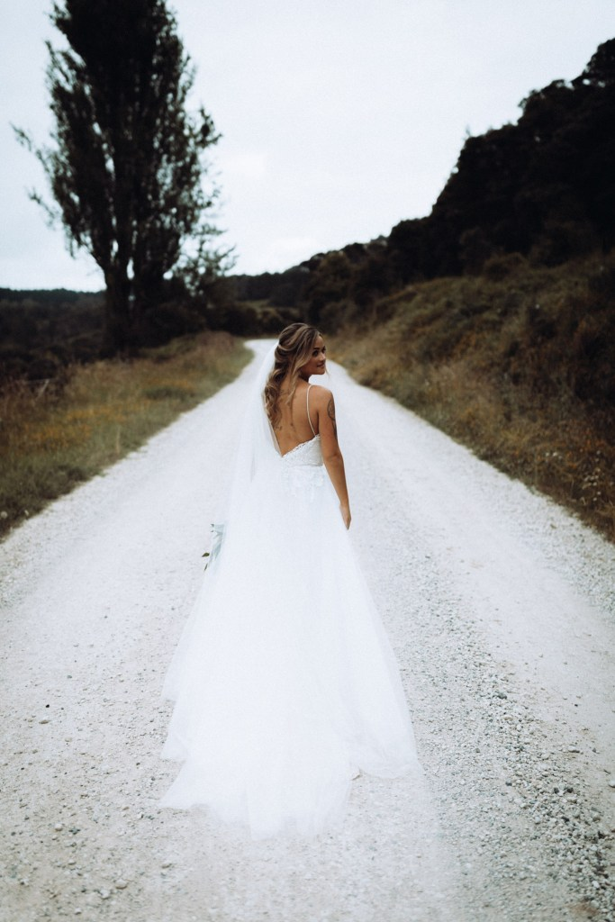 A bride in a wedding dress turns as she walks down a gravel road