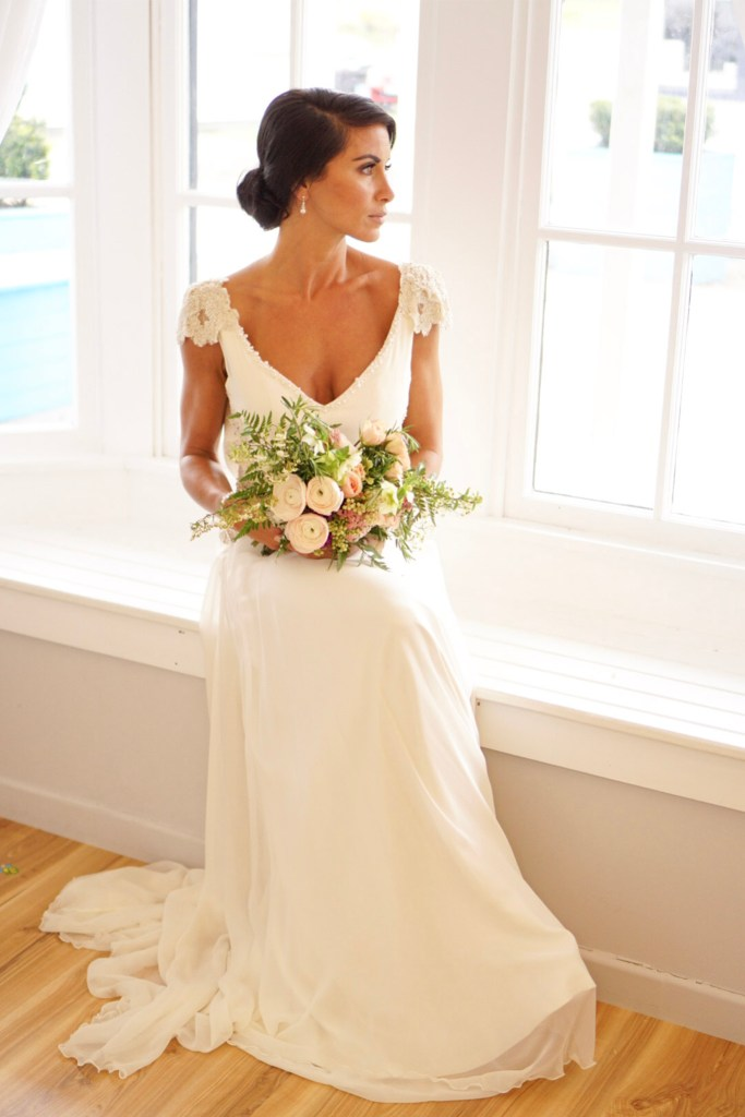 A woman wearing a white bridal gown sits by a window looking outside