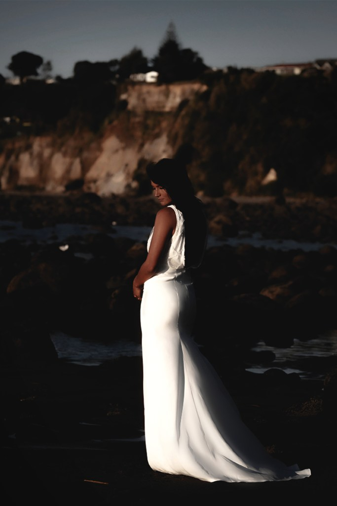 A woman in a white bridal gown standing outside near the water on a beach