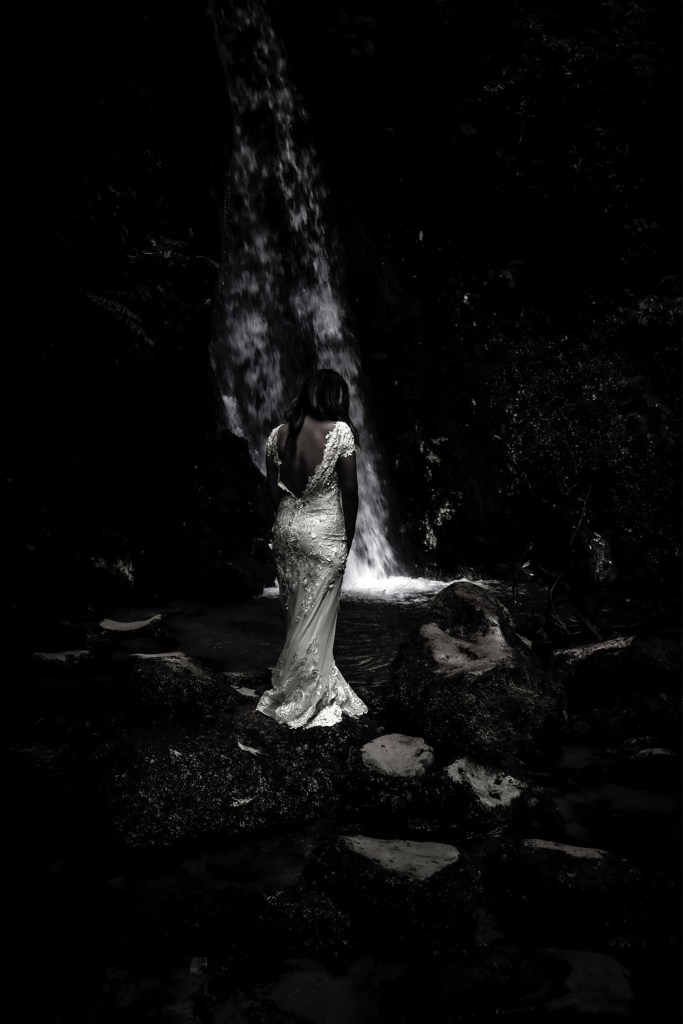 A woman in a white bridal gown standing on a rock with a waterfall in the background