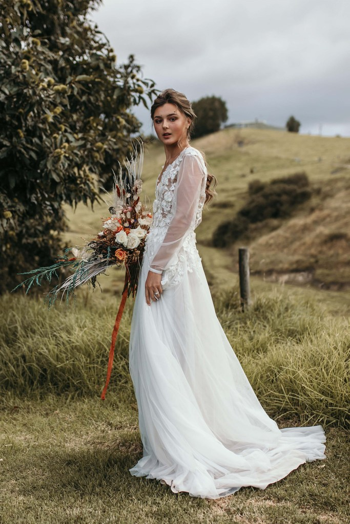 A young woman wearing a wedding dress stands in a field whilst holding flowers