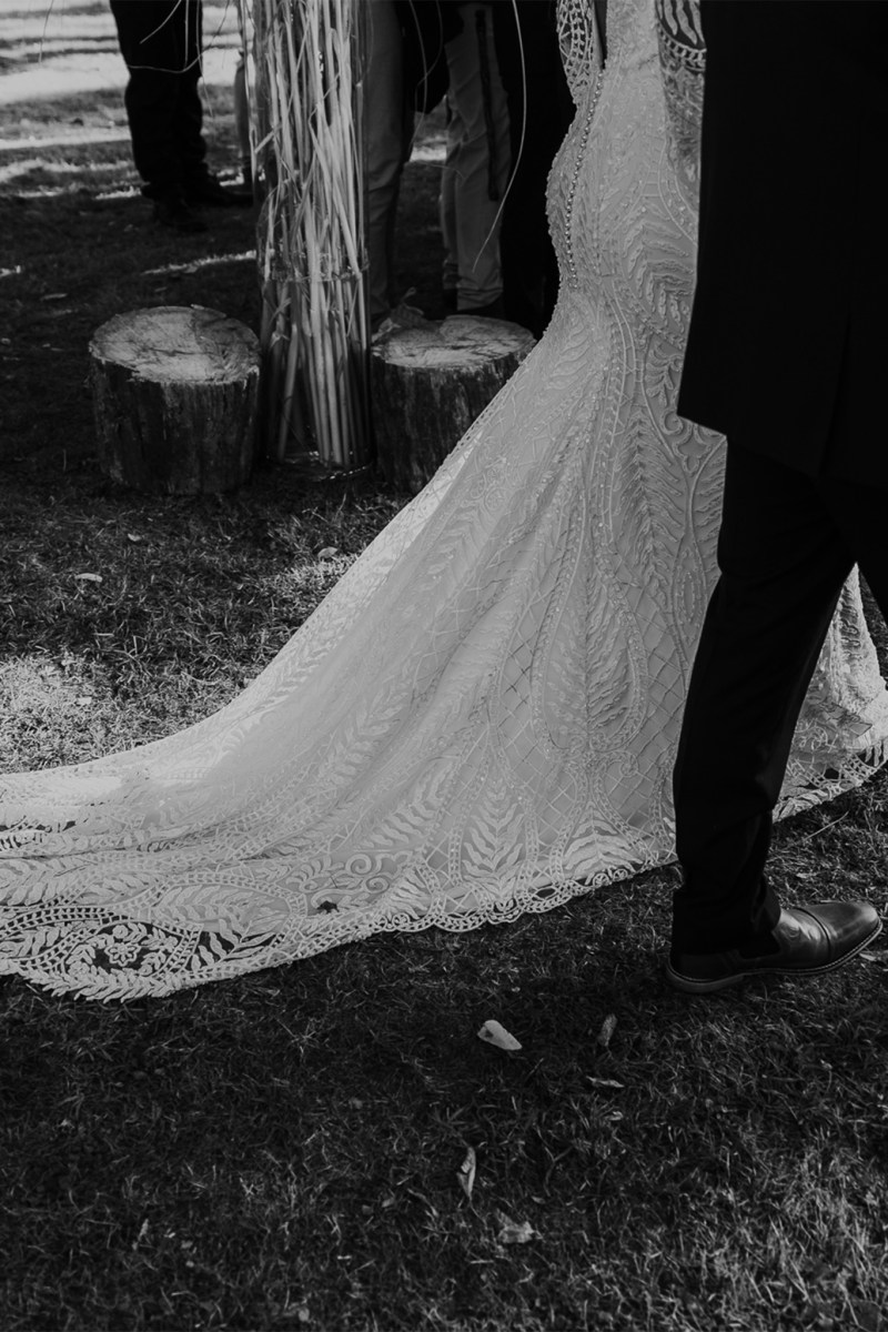 The back of a detailed bridal gown as the bride walks down the aisle