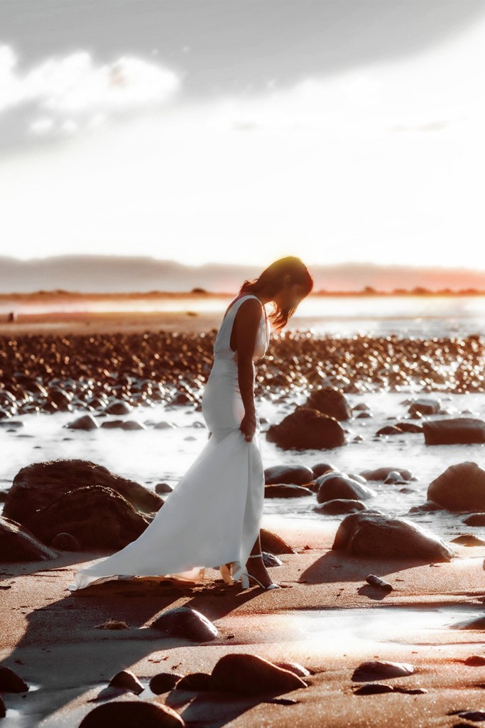 A woman in a white wedding dress walking on sand with water in the distance