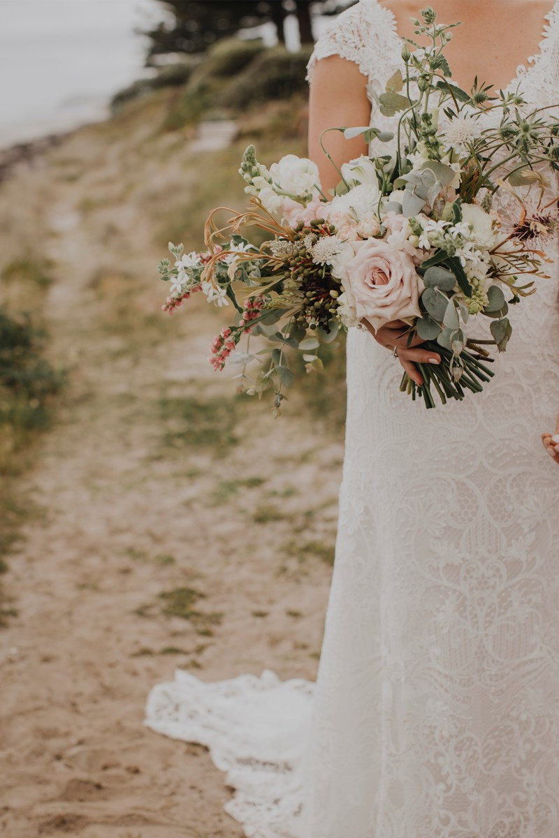 A close up of bridal gown flowers held by a bride
