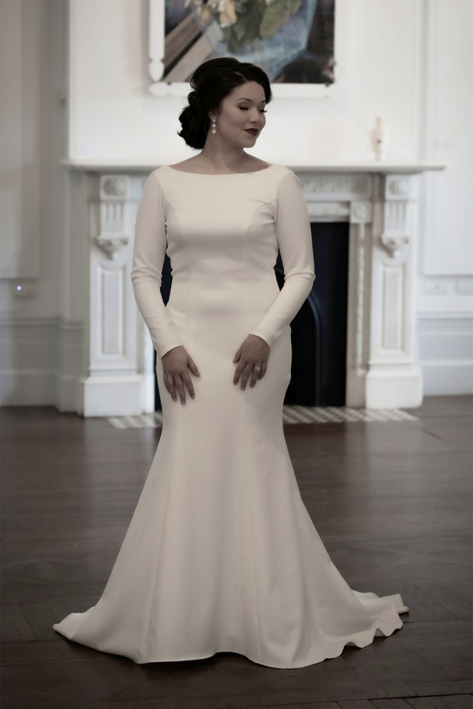 A woman in a slim, white bridal gown stands in a room with wooden floors