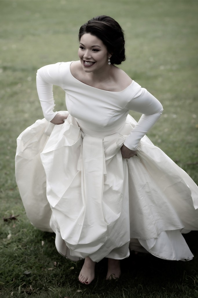 a woman in a white bridal gown smiles as she walks up a lawn