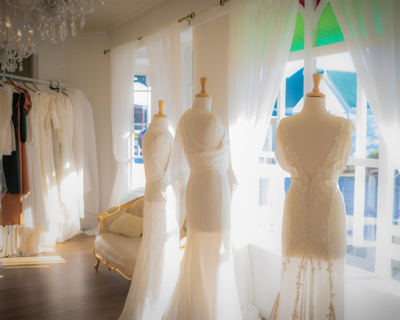three bridal gowns on mannequins close to a bridal shop window