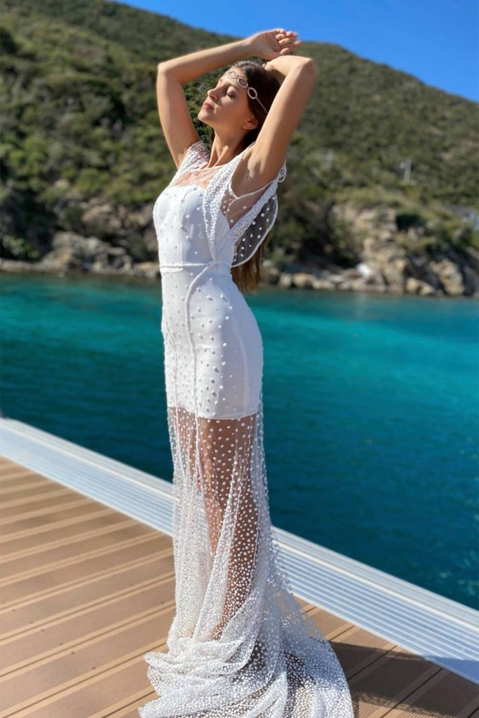 a woman in a white bridal gown raises her arms as she stands on a boat by the water