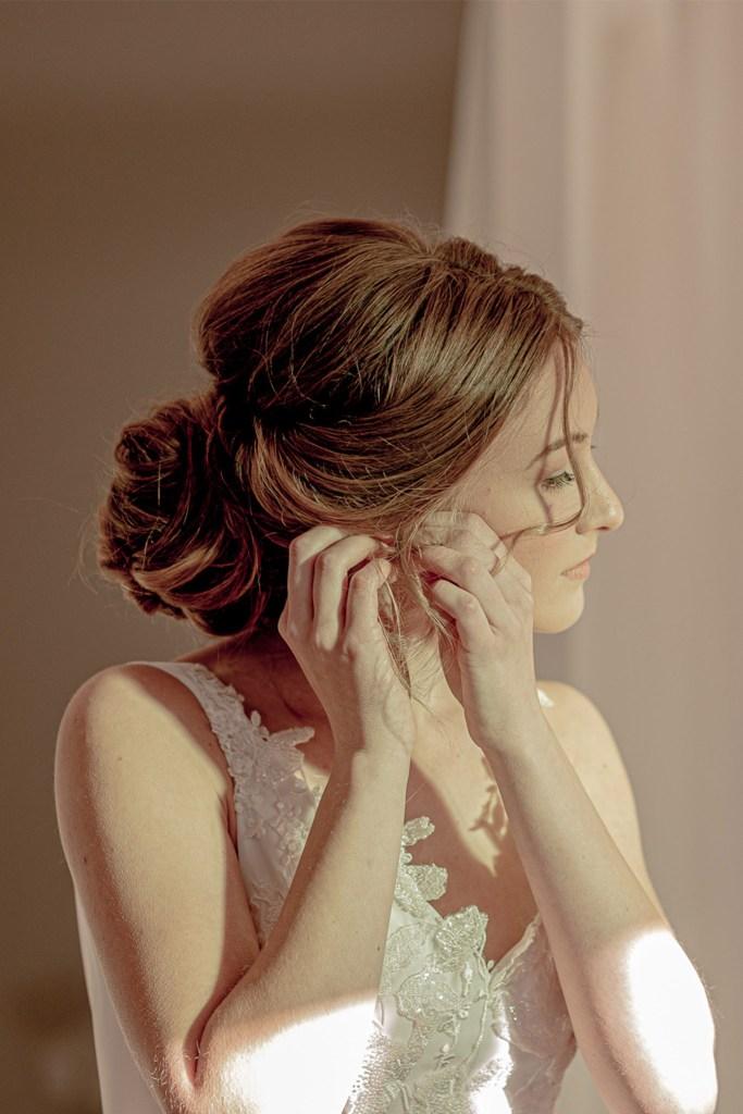 A woman wearing a white wedding dress adjusts an earing