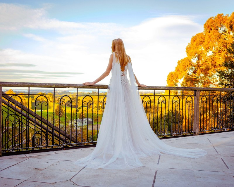 A woman in a white wedding dress stands on a balcony looking out to the countryside