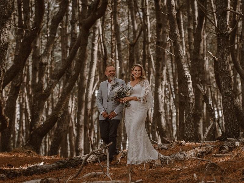 A bride walks in her wedding gown through a wood