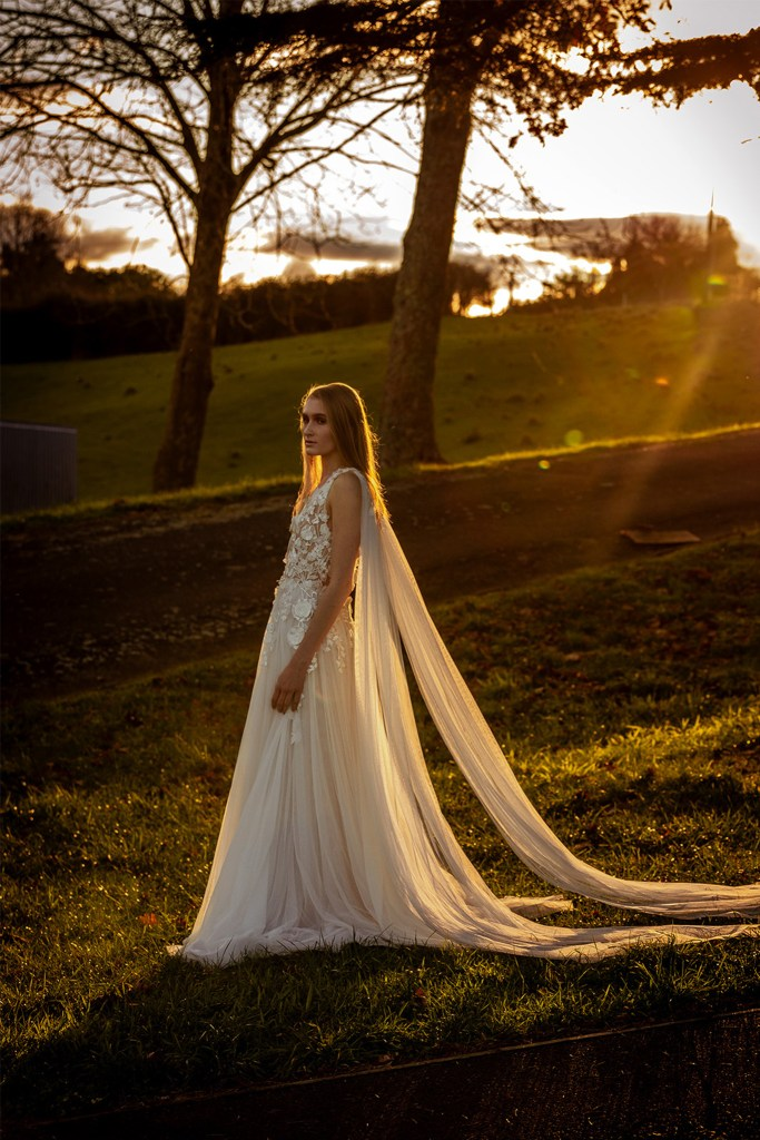 A woman in a white bridal gown stands on grass as the sun sets
