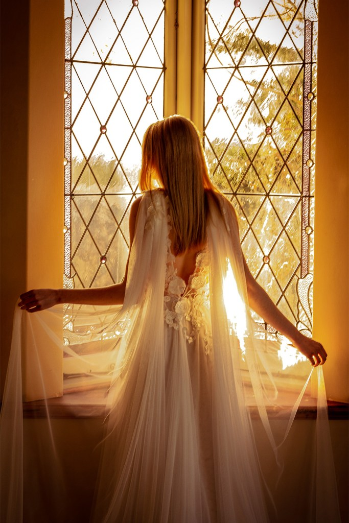 A woman stands in front of a window as she wears a bridal gown, as the sun sets