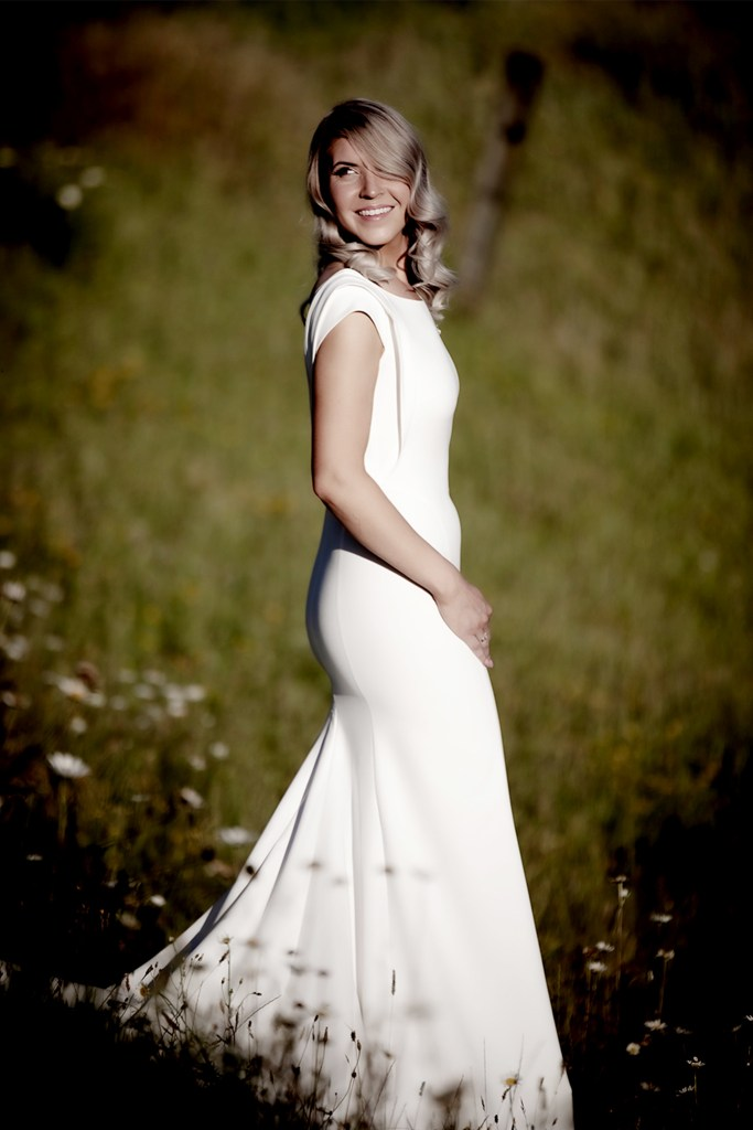 A woman wearing a white bridal gown in a field, smiling as she turns