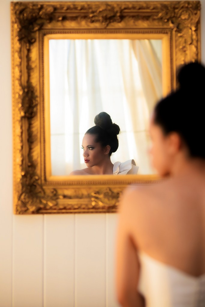 A woman's reflection in a mirror as she turns her head
