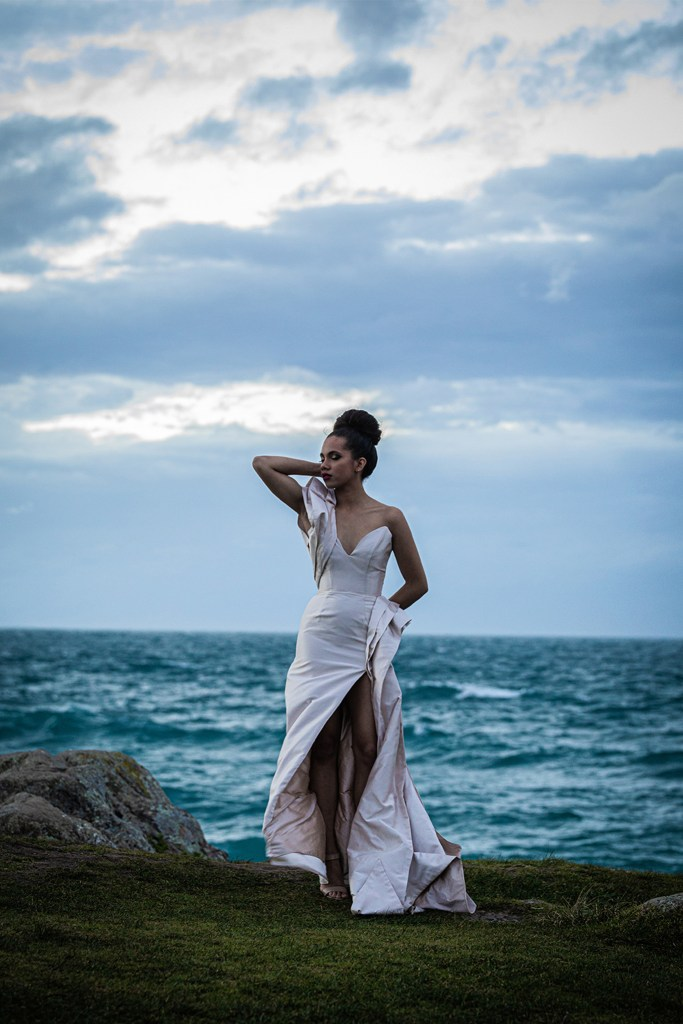 A woman in a bridal gown stands by the sea