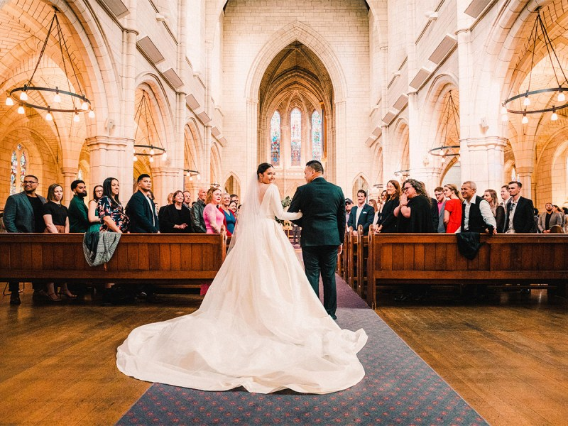 A woman in a white bridal gown smiles as she walks down the aisle of a large church
