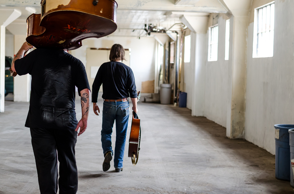 Walking away with instruments in their hands, Nathan Kalish in The White Wall Studio Warehouse for Season 2.
