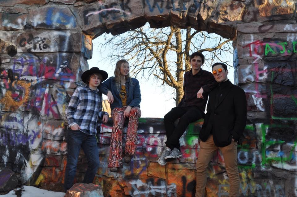 4 members of Granola pose at a grafitti wall