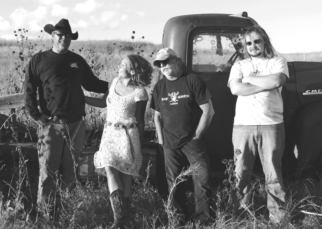 Black and white photo of The Hidden Timber Band posing by an old pick-up truck in a field