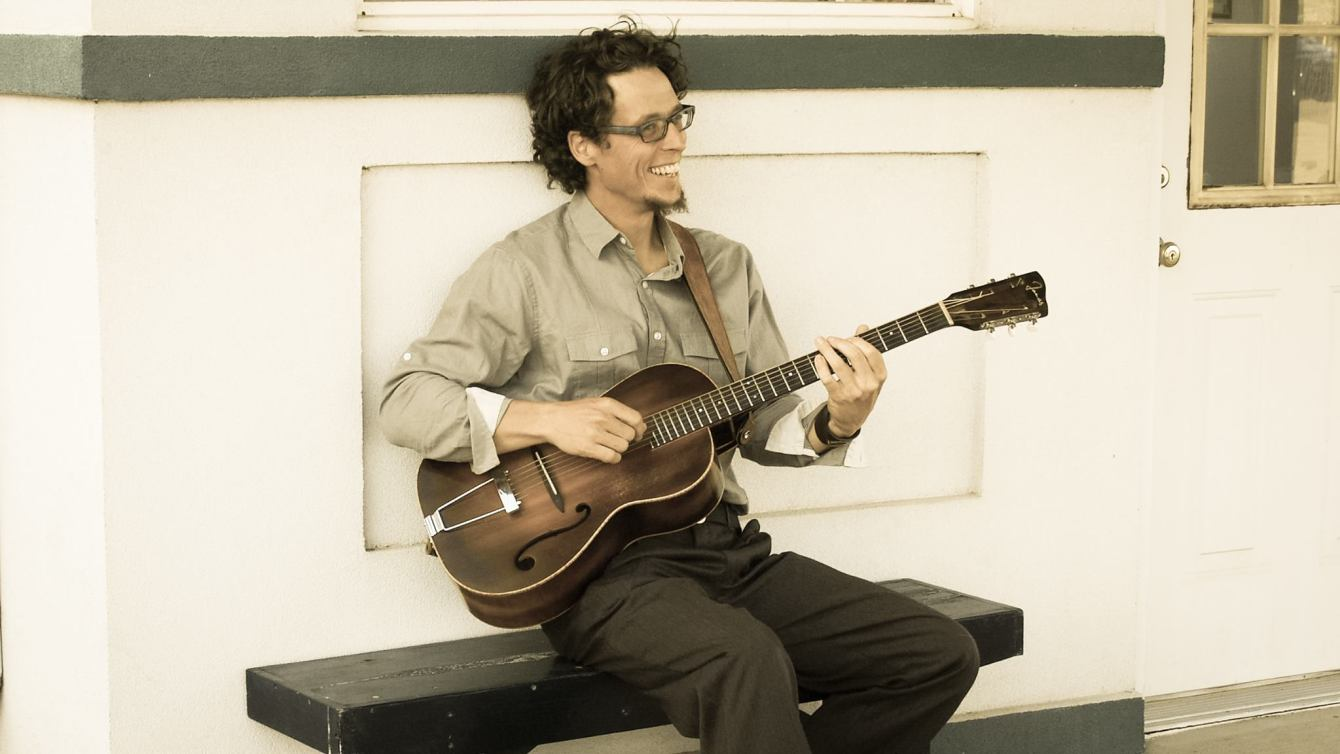 Nashville's Feathered Mason sits on a bench as he smiles and plays his acoustic guitar