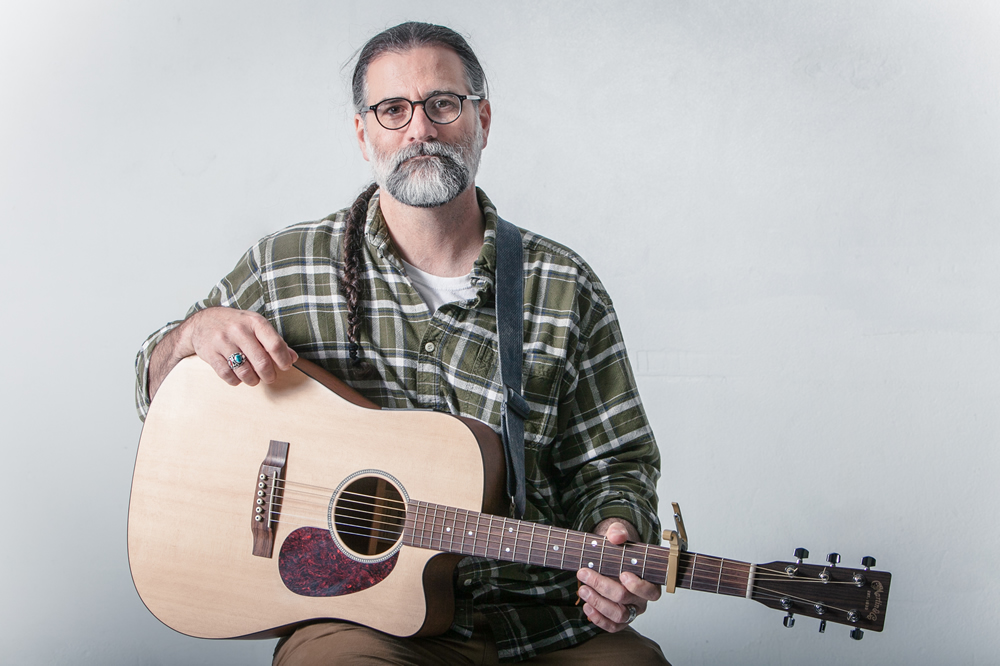Scott Simpson from Spearfish, SD poses with his acoustic guitar at the White Wall studio in Sioux Falls