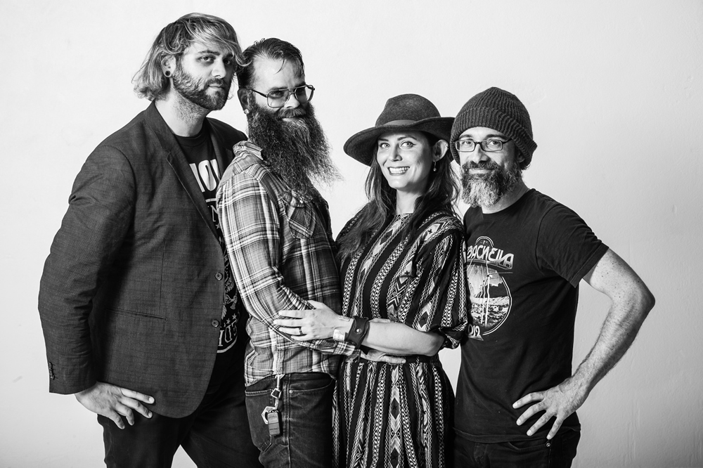 4 members of the indie rock band, Ms. Shevaughn & Yuma Wray smile in a black & white photo at The White Wall Sessions
