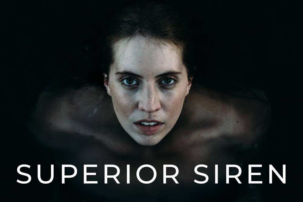 A naked woman in dark water looking directly at the camera with Superior Siren bold stated below