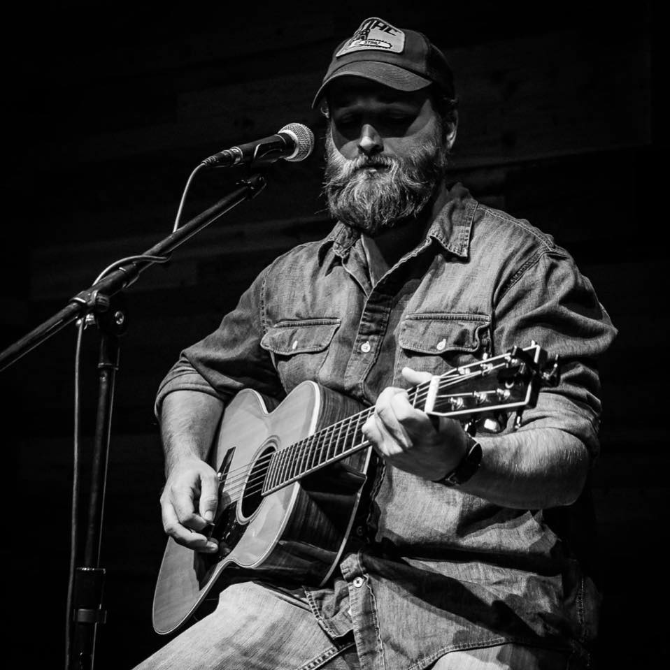 Black and white photo of David Allen playing acoustic guitar