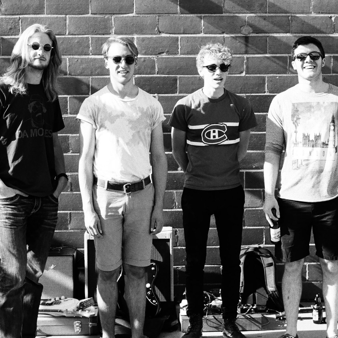 4 members of Sioux Center's The Aircraft smile with sunglasses on in front of a brick wall