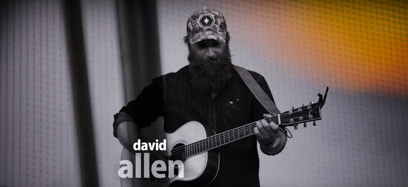 Hatton, ND's singer-songwriter David Allen looks at his fingers on the frets of his guitar.