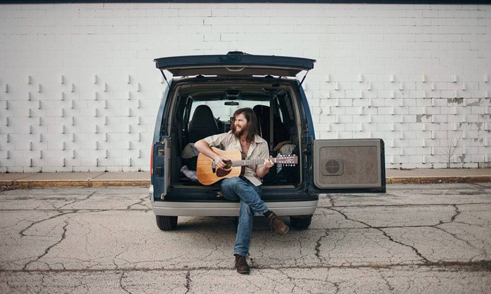 Luke Callen sits playing guitar with one front on the ground in the back door of a minivan