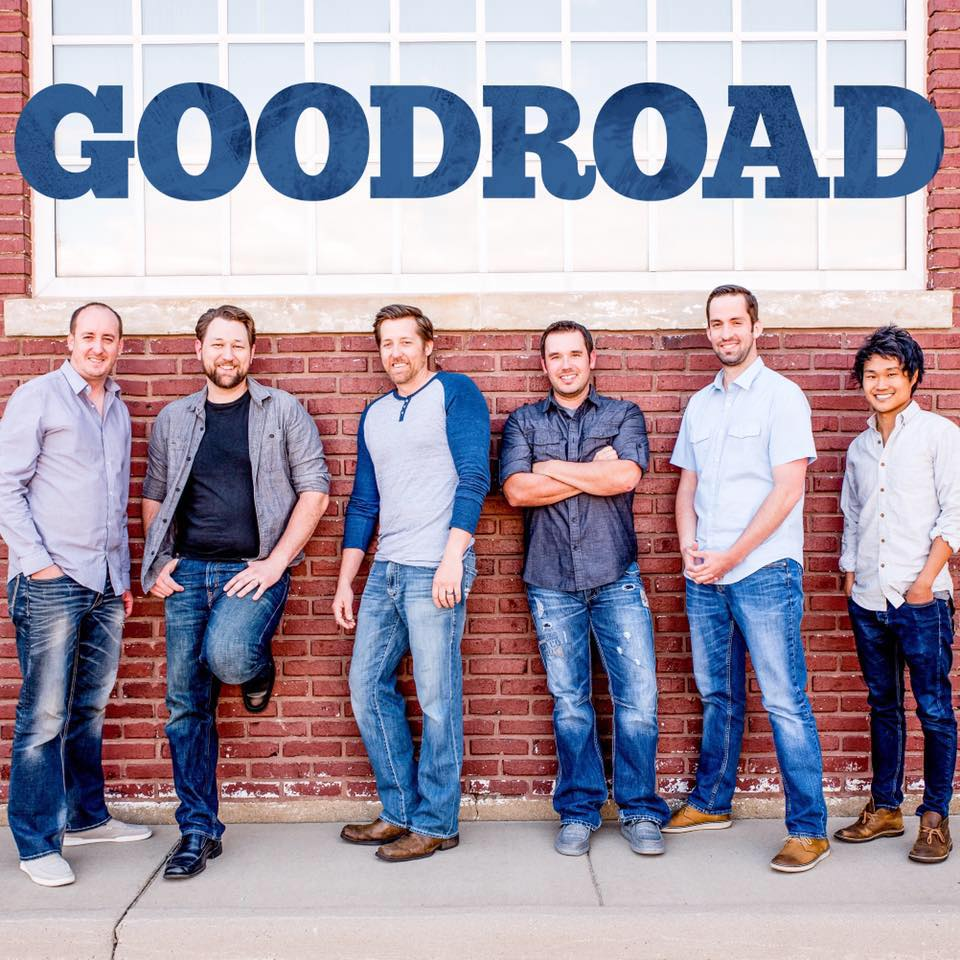 6 members of Sioux Falls' pop rock band Goodroad standing in front of a brick building with GOODROAD hovering above their heads.